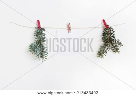 Sheet of blank note paper hanging on the wooden cloth pegs and rope with green fir branches, Christmas mockup template.
