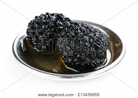 Black truffle mushrooms in oil, isolated on white.
