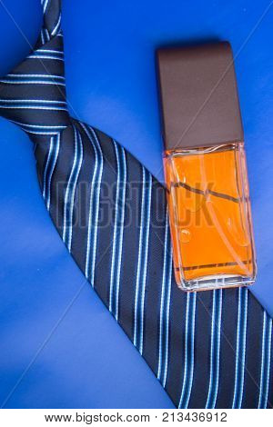 Perfume bottle with tie on blue background. Accessories for man.