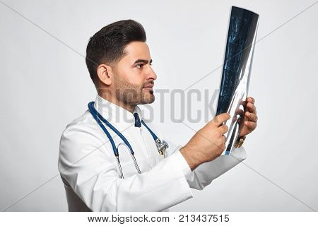 Studio shot of a bearded male doctor with a stethoscope examining MRI scan