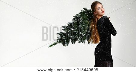 Young glamour russian woman with winter christmas tree decoration in fur hat skin vulpes lagopus under heavy snow. New year concept background
