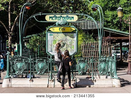 Paris France - July 03 2017: Young tourists in Paris using map and looking for the direction at the entrance to the Paris Metropolitain (subway) at the Cite metro station.