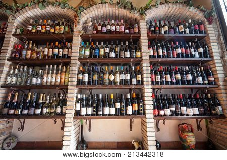 TAORMINA, ITALY. April 3, 2015: Winery shop. Wine store shelves. A shelf inside a wine shop in Taormina in Sicily, Italy. Three brick arches.