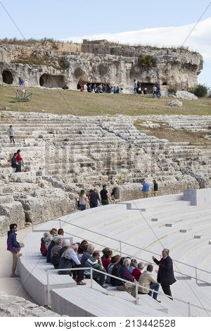 SYRACUSE, ITALY. April 3, 2015: Greek Theatre of Syracuse, Italy. Group tour with guide. Travel guide with tourists group sitting on ancient steps.
