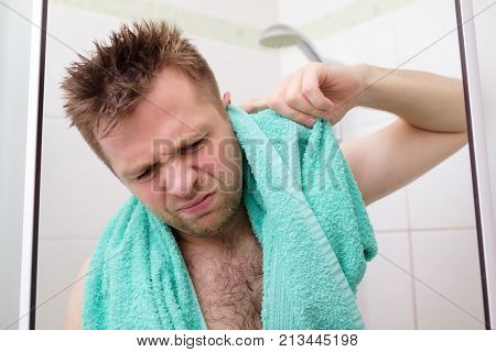 Young caucasian man cleaning his ear while taking a shower and standing under flowing water