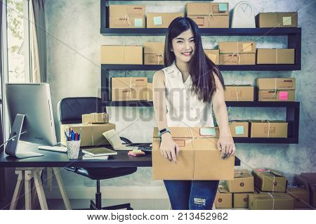 Young asian teenager owner business woman work at home for online shopping holding and present the product with office equipment entrepreneur and alpha generation life style concept