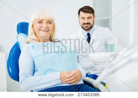 Ready for teeth cure. Waist up of cheerful patient sitting on dental chair with hands kept together while the doctor sitting in the background