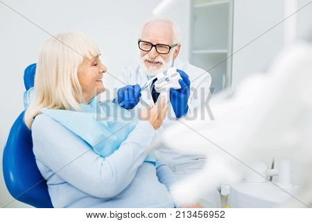 Have a look. Smiling professional dentist looking at the patient and showing false teeth while the patient expressing interest