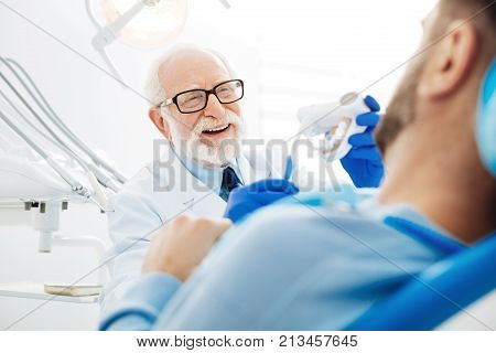 Splendid mood. Close up of skilled doctor being pleased while holding false teeth in hand and communicating with the patient