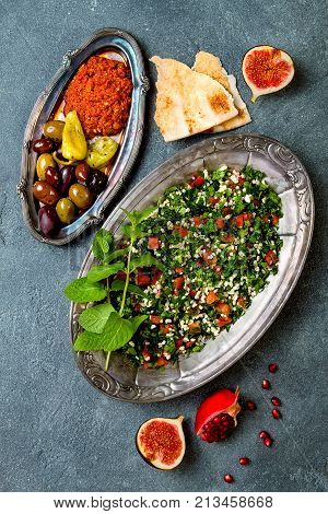 Middle Eastern traditional dinner. Authentic arab cuisine. Meze party food. Tabbouleh muhammara olives. Top view flat lay overhead