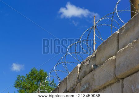 Barbed Wire Spiral Bruno On Top Rough High Stone Walls.