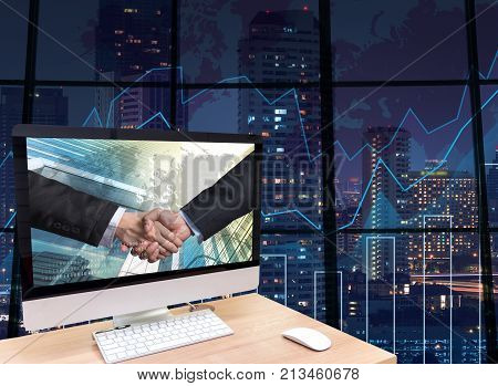 the computer on the wood table with Hand shake between businessman at the screen on the trading graph over the blurred photo of cityscape backgroundElements of this image furnished by NASA