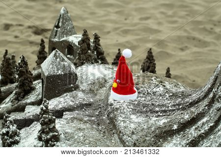 Beautiful sandcastle or sculpture miniature building with red santa hat on grey sandy beach surface outdoors on sand texture background