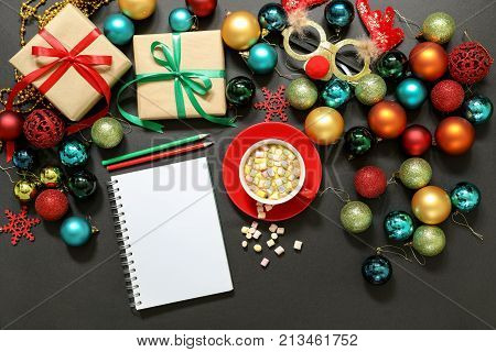 Christmas tree toys different colors balls gifts deer mask notebook pencils cup of coffee with marshmallows on a dark background Christmas New Year holidays preparation concept. Top view.