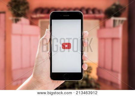 Chiangmai Thailand- July 8 2017:Man hands holding a Iphone 6s mobile phone which displays the Youtube app on the touch screen.
