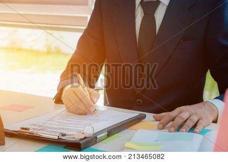 businessman hand holding pen for To sign house and land trading signals at his workplace.