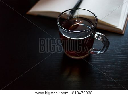 A notebook with blank pages a black pen glass mug with teabag on dark desk