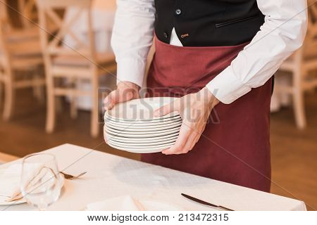 Cropped image of Waiter putting pile of plates on the table