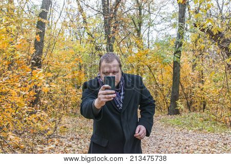 Smiling Young Man In Coat, Taking Pictures On Phone. A Man Is Looking At The Phone.