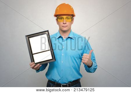 Engineer award mockup. Best worker certificate. Foreman in a helmet holding in one hand empty blank photo frame and showing thumbs up gesture sign by another hand. Gratitude concept. Grateful letter.