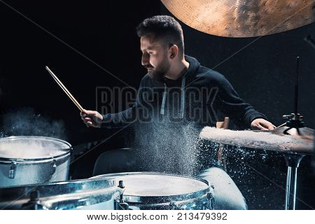 Drummer rehearsing on drums before rock concert. Man recording music on drum set in studio with show effect in the form of flour