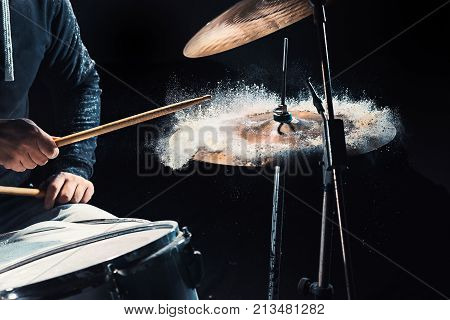The hands of drummer rehearsing on drums before rock concert. Man recording music on drum set in studio with show effect in the form of flour
