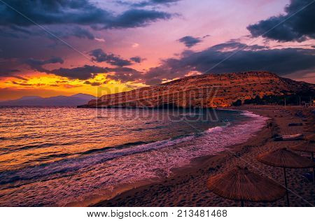 Sunset at Matala beach on Crete island, Greece. Tourists relax and bath in crystal clear water of Matala in south of Creta. There are many caves near the beach.