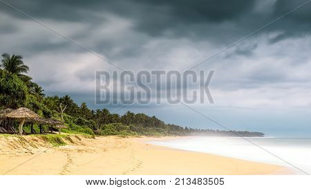 Sandy tropical beach with long exposure for blurred water and ocean waves milky wave effect