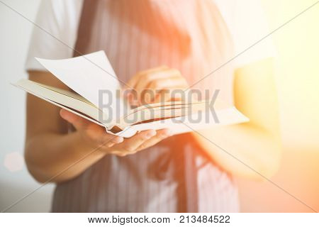 Girl wearing grey apron and reading book. Lifestyle concept. Festive background with bokeh and sunlight
