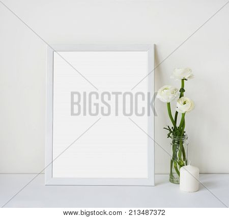 Empty white frame with place for text on the white wall and table bouquet of flowers ranunculus and candle. Scandinavian style room interior. Template mock up for paintings or photographs
