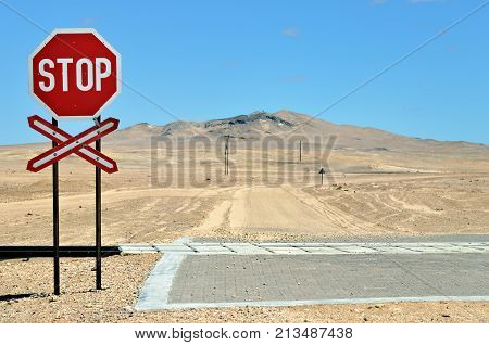 Dirt country road in Namib desert. There are railroads across the road. Rail crossing is marked by road signs. Namibia Africa