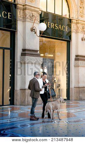 MILAN ITALY - NOVEMBER 3 2017: Fashionable couple in Vittorio Emanuelle gallery in Milano on November 3 2017 in Milan Italy