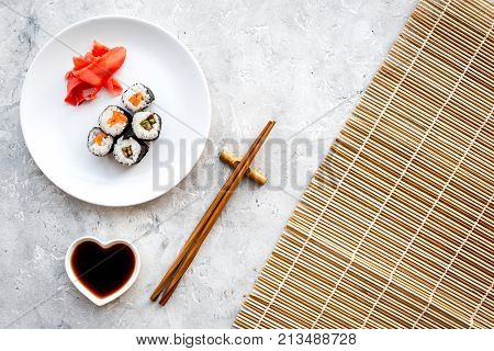 Sushi roll with salmon and avocado on plate with soy sauce, chopstick, wasabi on mat on grey stone background top view.