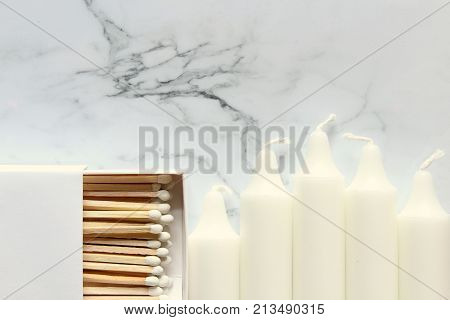 White match book and matches with white candles frame white marble copy space.