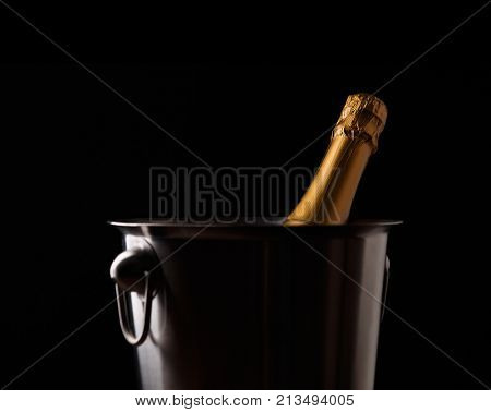 Picture of bottle of champagne in iron bucket on black background
