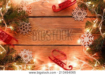 Picture on top of wooden surface with burning garland, branches of spruce, Christmas toys, snowflakes. Empty place for text.