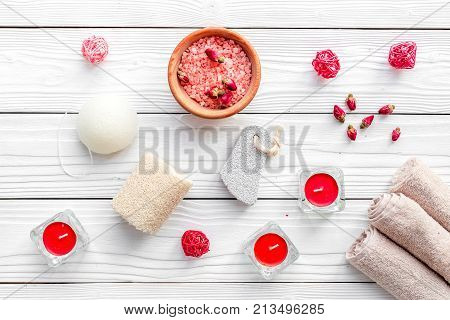 Romantic set for foot spa. Candles, salt, pumice stone, soap on white wooden background top view.