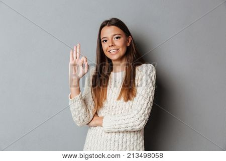 Portrait of a happy smiling girl in sweater standing and showing ok gesture isolated over gray background