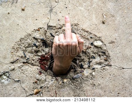 middle finger through concrete wall dark emotion