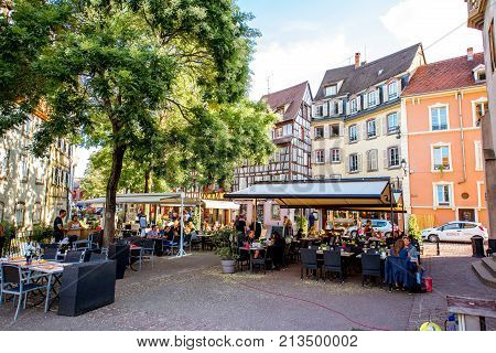 COLMAR, FRANCE - July 26, 2017: Street view on the beautiful old buildings with cafes and restaurants in the famous tourist town Colmar in Alsace region, France