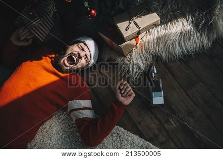 Another picture of an adult guy lying on the floor near pine tree with tree toys and Christmas gifts this sunny morning. After parting all night long this man has a terrible hangover. And he is not happy the sunlight makes him get up. Cut view