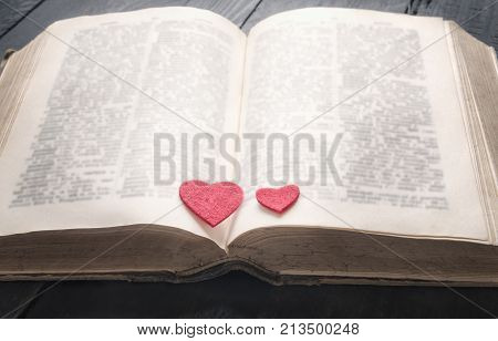 Antique book and two hearts on it - Two red hearts on the pages of an old open book displayed on a vintage black table. A concept for the love of education a romantic novel or a love story.