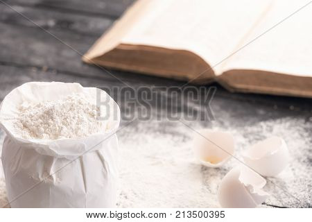 Bag of flour and a cookbook - Open bag of wheat flour on a rustic wooden table covered with flour egg shells and an open recipe book in the background.