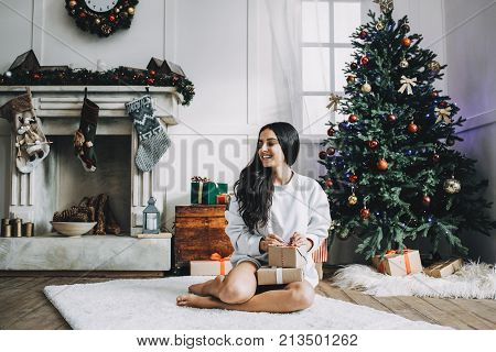 Beautiful girl in white sweater is sitting on big cozy carpet and holding boxes of gifts for her beloved. On the back there are a white fireplace covered with garlands and socks and green pine tree full of Christmas toys. Christmas is coming.
