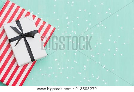 Top view on Christmas gifts wrapped in striped gift paper decorated with ribbon on turquoise wooden background with sparkling stars. New Year holidays and celebration concept
