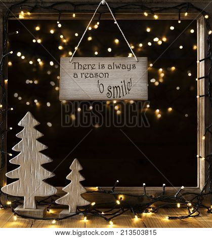 Sign With English Quote There Is Always A Reason To Smile. Window Frame With Lights In The Night In Background. Christmas Decoration Like Christmas Tree And Fairy Lights.