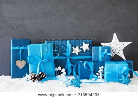 Concrete Wall With Copy Space For Advertisement. Blue Christmas Gifts On Snow With Decoration Like Stars And Fir Cone.