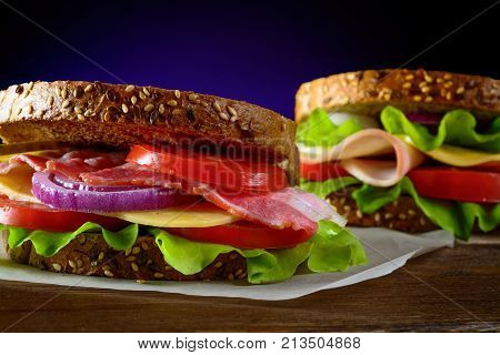 Healthy sandwiches freshly prepared with bacon, tomato, ham, cucumber, cheese, onion on whole grain wheat toast on wooden table.