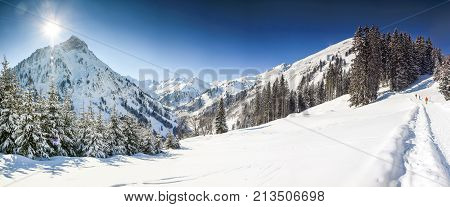 Three people hiking in mountains winter landscape with deep snow on clear sunny day. Alps, Bavaria in Germany.