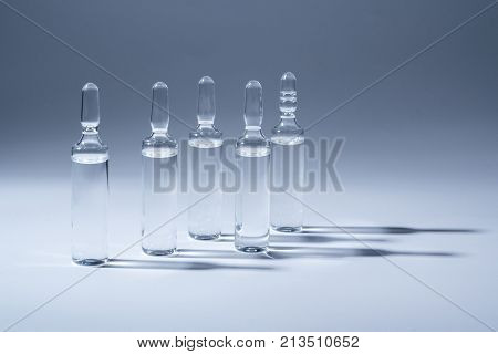 Medical ampules for injection isolated on blue background